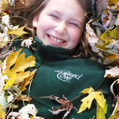 Fernwood Cove Camper playing in the fall leaves